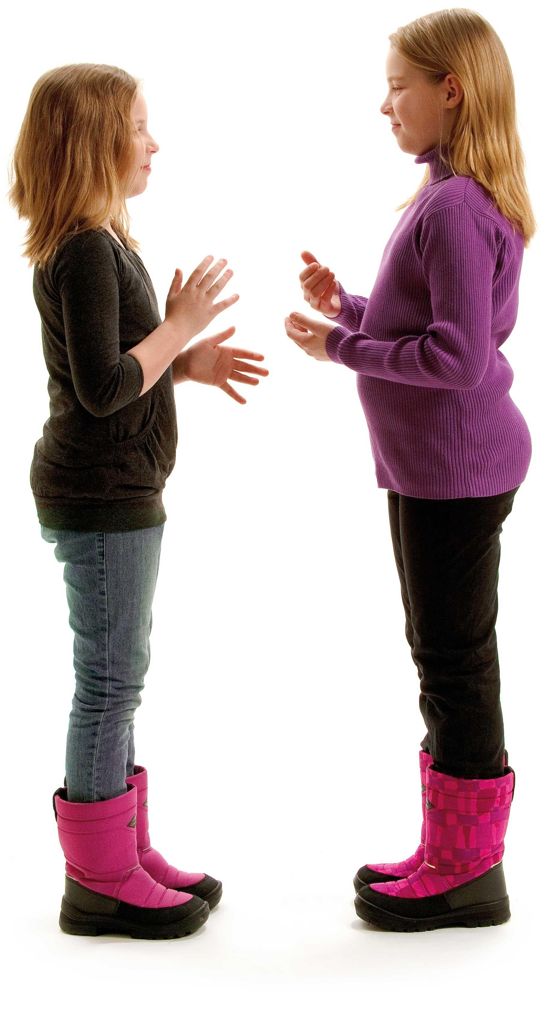 Kaksi nuorta tyttöä seisoo vastakkain, päällä sisävaatteet, jalassa talvikengät. Molemmilla on kädet koholla valmiina viittomaan.