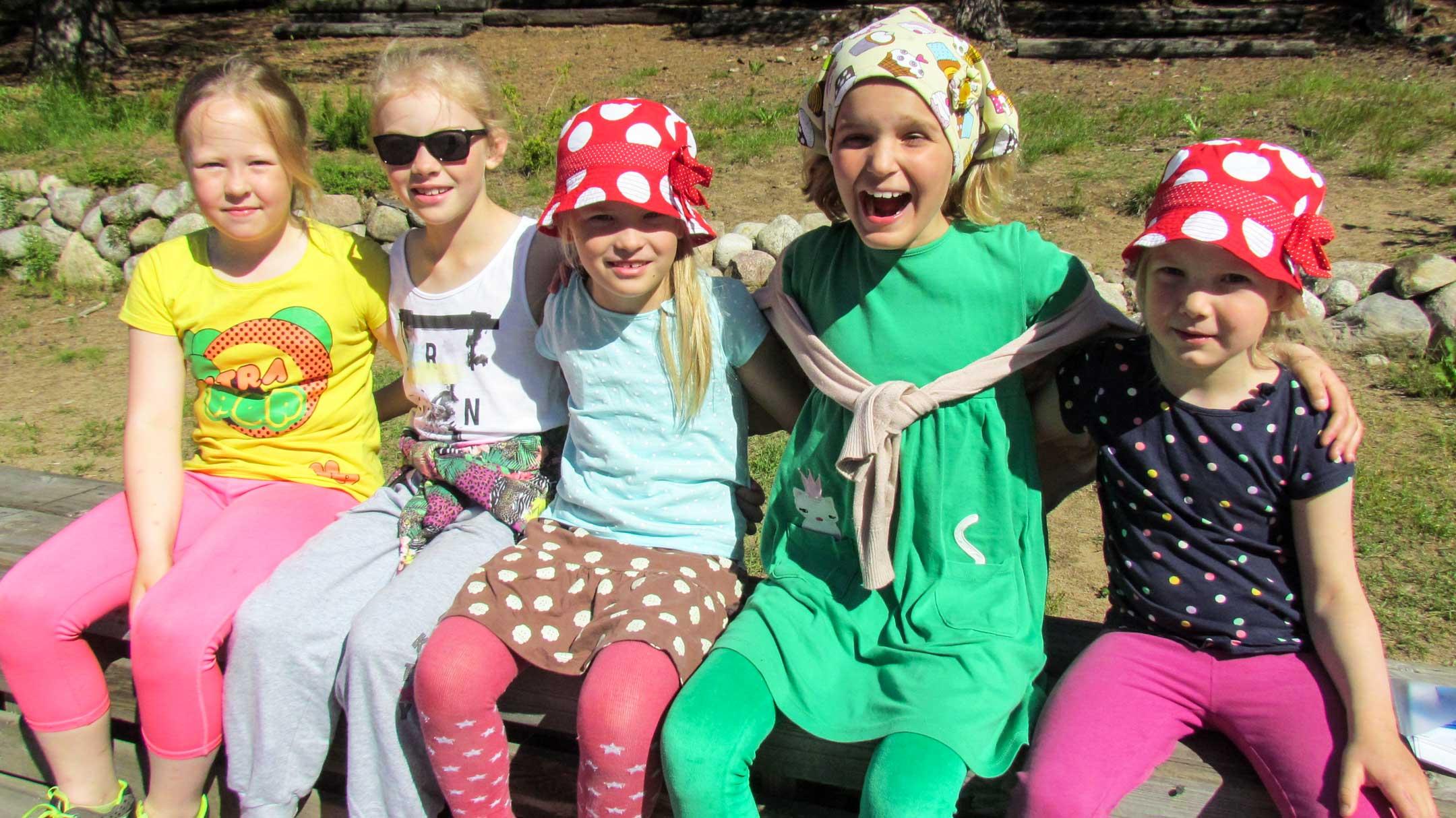 Viisi lasta istuu ulkona penkillä vierekkäin, kaikilla on värikkäät kesävaatteet, sää on aurinkoinen.