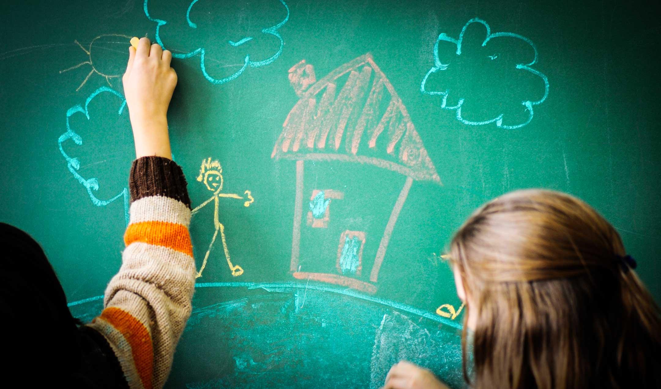 Kaksi lasta seisoo liitutaulun edessä, piirtävät värikkäillä liiduilla, piirrettynä jo talo, tikku-ukko, pilvi ja aurinko.