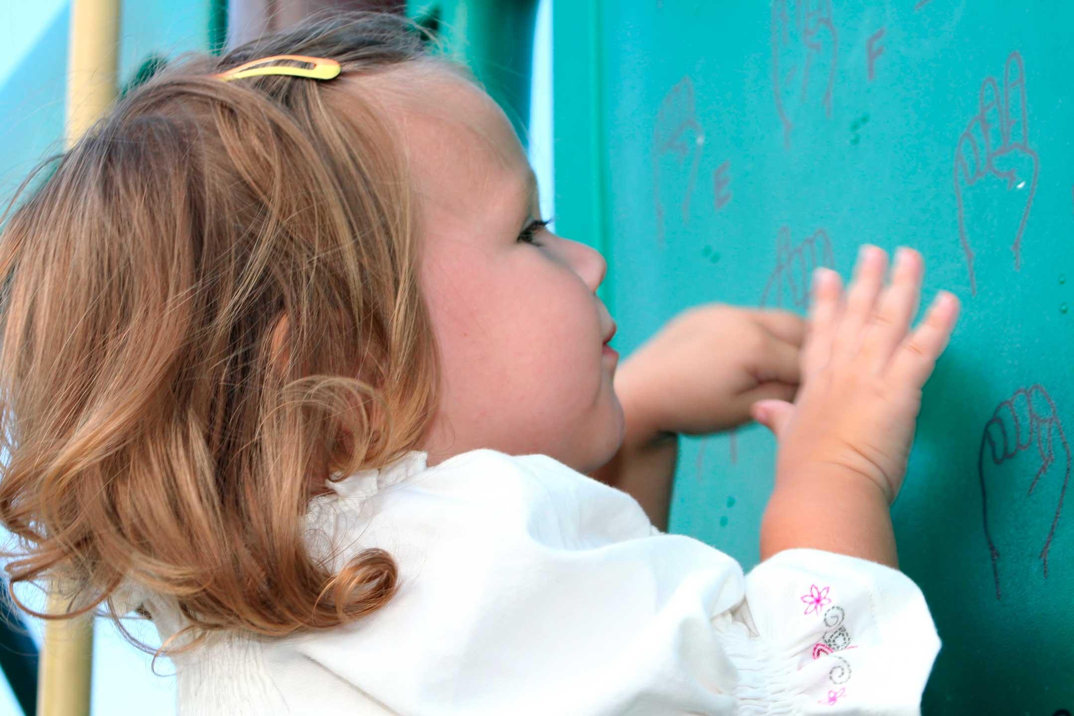 Seinä, johon on painettu viittomakielen sormiaakkosia. Seinän edessä pieni lapsi koskettelee seinän kuvia ja yrittää muodostaa sormillaan kuvissa olevia sormiaakkosia.