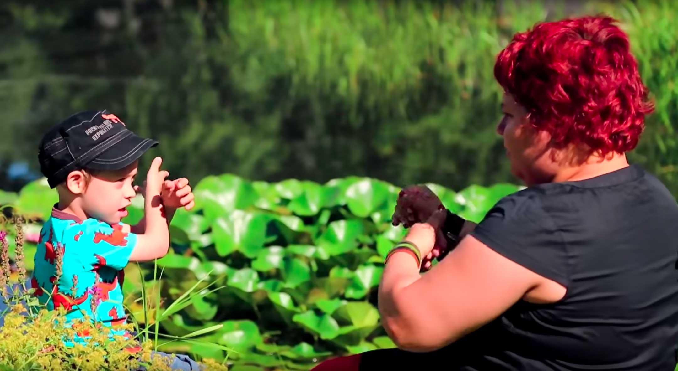 Punatukkainen nainen ja pieni poika, Verne, istuvat vihreiden kasvien keskellä ja keskustelevat viittoen. Samat henkilöt esiintyvät lukuun kuuluvassa videossa.