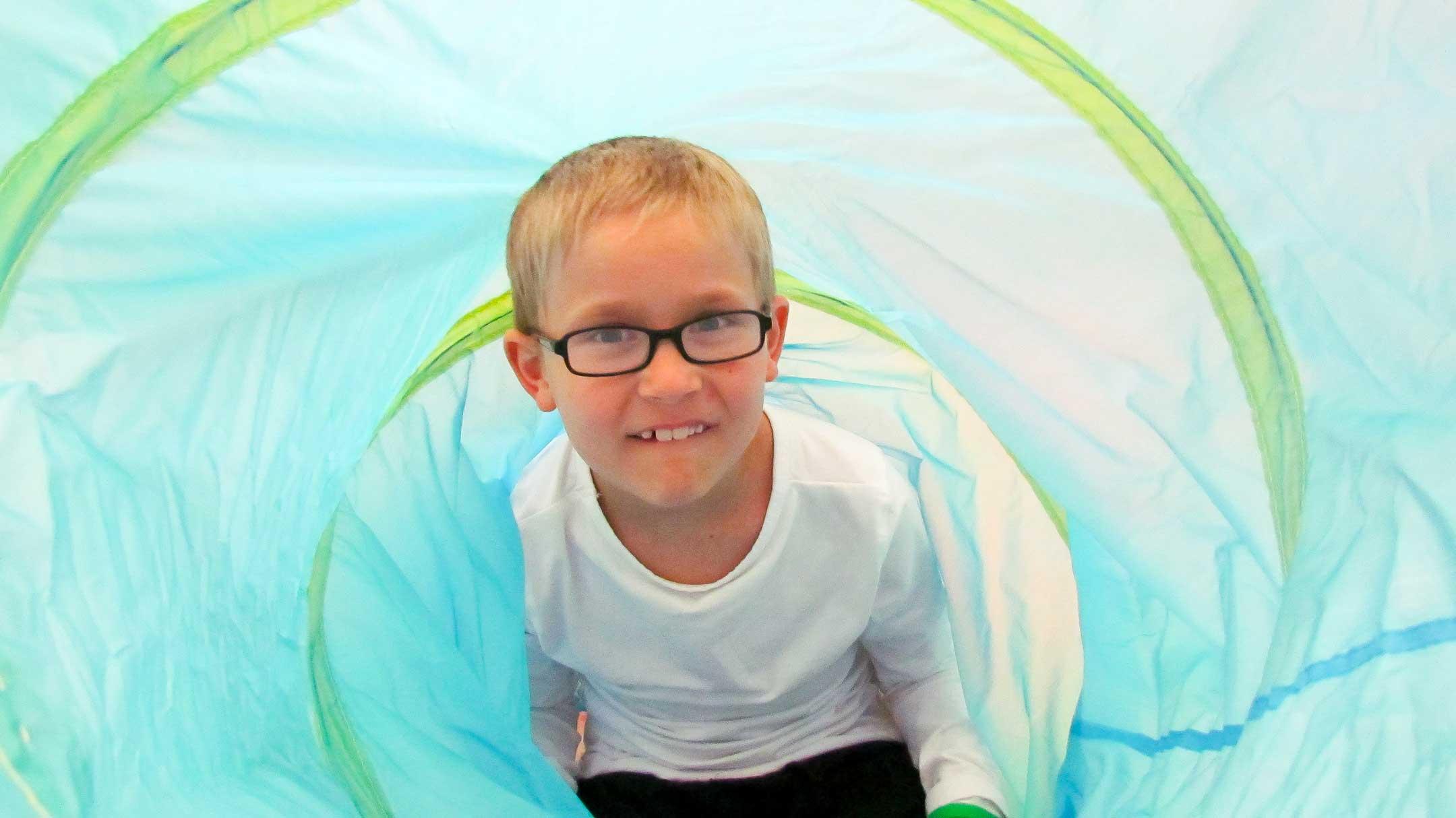 Vaalea lyhyttukkainen lapsi valkoisessa paidassa sinivihreän putken sisällä katsoo suoraan kuvaajaa.