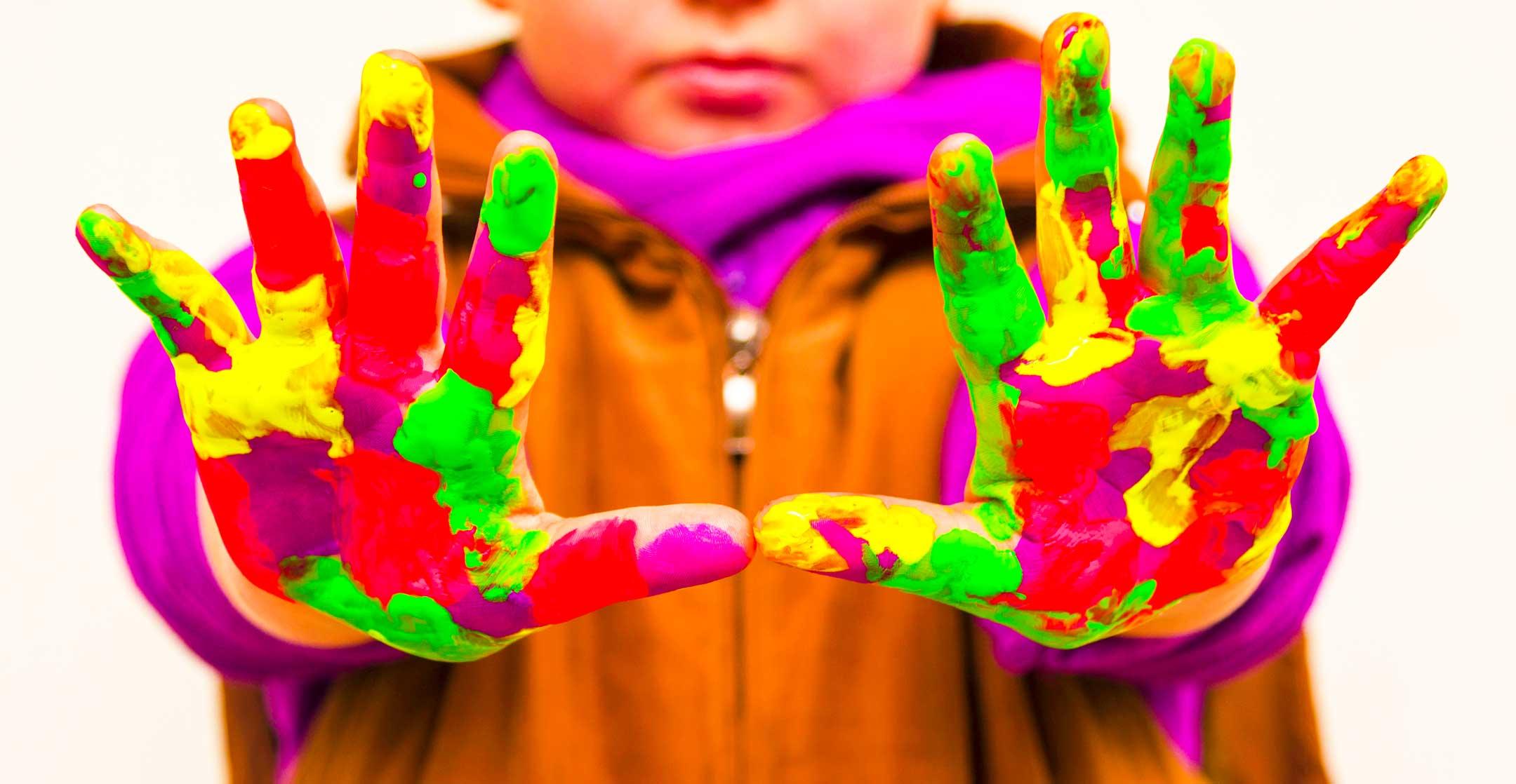 Värikkäissä vaatteissa oleva lapsi on ojentanut kämmenet kohden katsojaa, kämmenet ovat kauttaaltaan maalattu erivärisillä maaleilla.